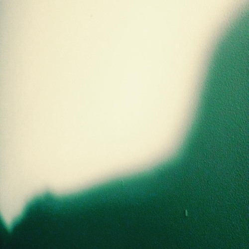 A grainy, abstract photo of a shadow against a plain wall