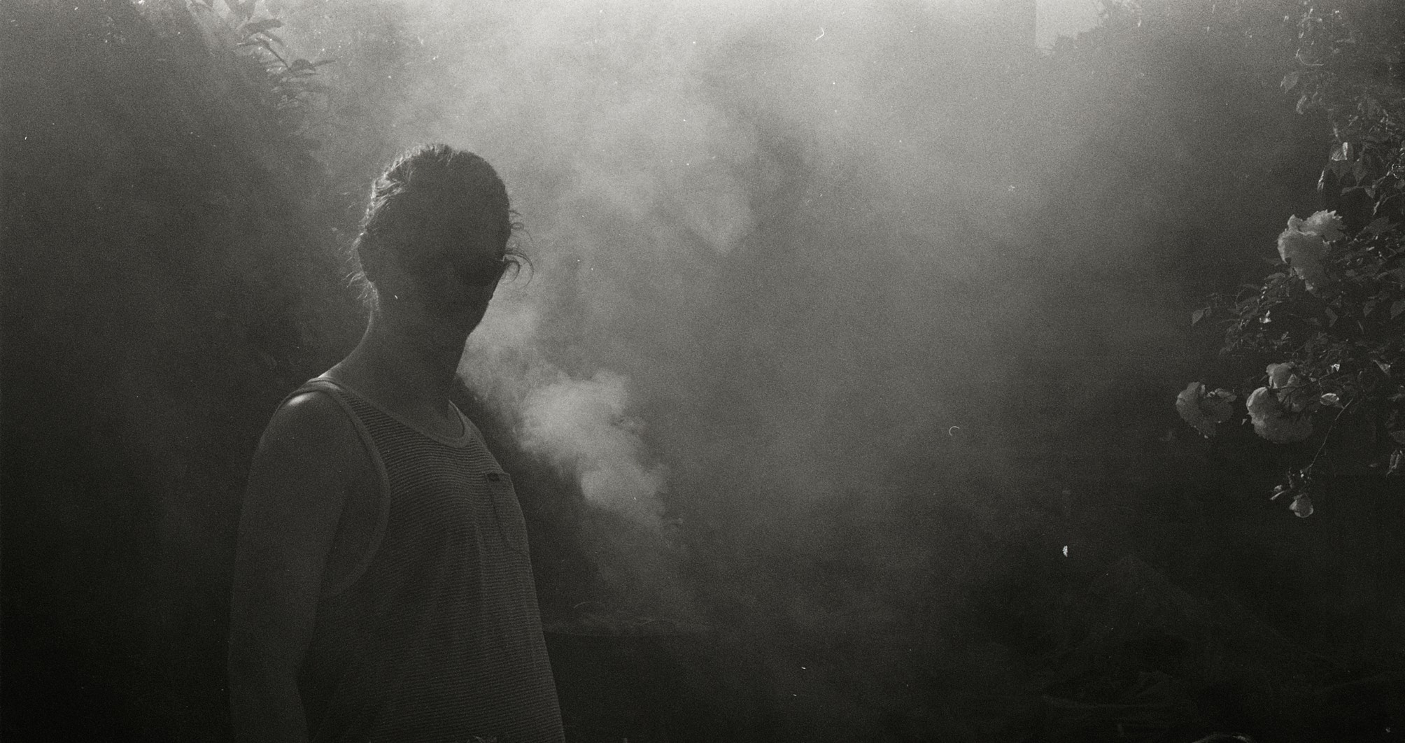 Black and white photo of Patrick Young, Raconteur, deep in BBQ smoke